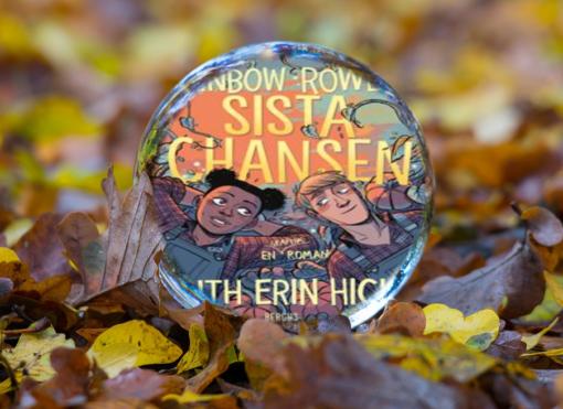 Omslaget till serieromanen Sista chansen av Rainbow Rowell och Faith Erin Hicks syns i en vattendroppe. Vattendroppen ligger på en höstlövstäckt mark.