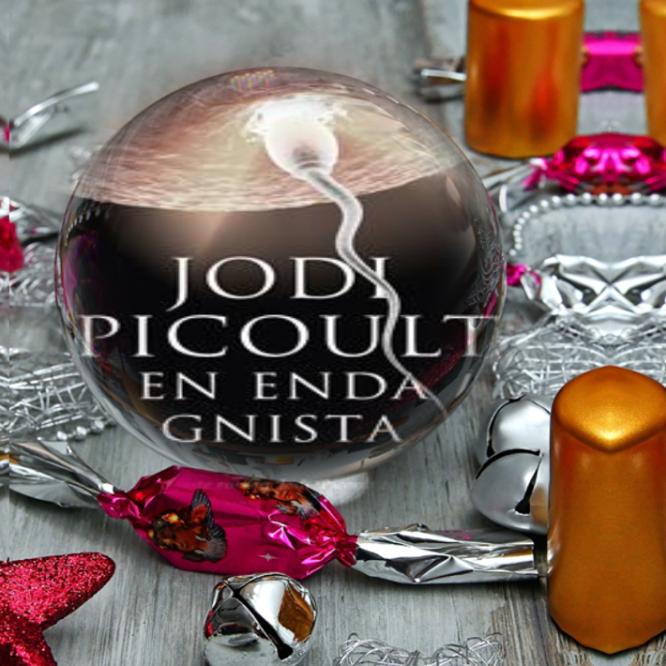 bokomslaget till boken en enda gnista av jodi picoult inuti en glaskula på ett träbord med ljus och nyårspynt utspritt runt sig.