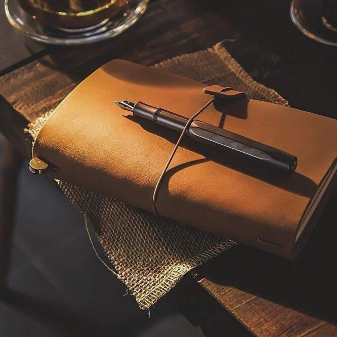 gammaldags läder anteckningsbok ligger på ett bord. Ovanpå boken ligger en reservoarpenna.
