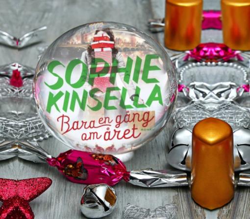 bokomslaget till boken Bara en gång om året av sophie kinsella inuti en glaskula på ett träbord med ljus och nyårspynt utspritt runt sig.