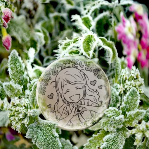 En glad serietecknad flicka som gör hjärttecken med händerna inuti en iskula. Iskulan är bland frosttäckta gröna blomblad.