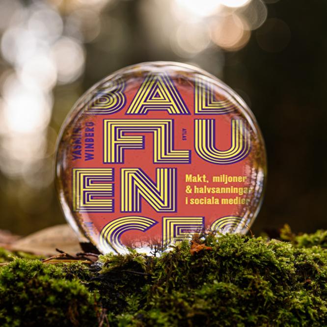 Omslaget till boken Badfluence: makt, miljoner och halvsanningar i sociala medier av Yasmine Winberg och Julia Lundin inuti en liten glaskula som är på en bädd av mossa.