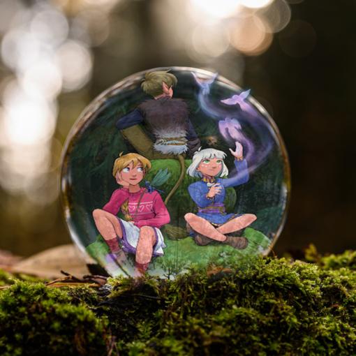 Sonja, Espen och Lotta från serien Norrsken av Malin Falch sitter på några stenklippor och utövar magi inuti en liten glaskula på en bädd av mossa.