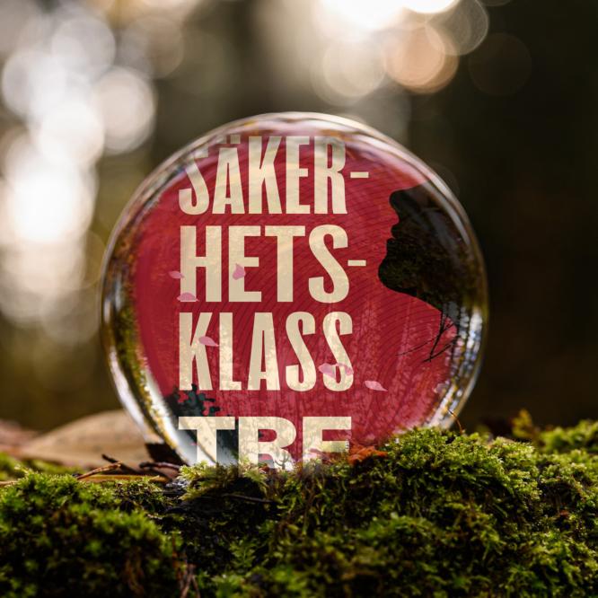 Omslaget till boken Säkerhetsklass tre av Kerstin Loenberg inuti en liten glaskula som är på en bädd av mossa.